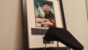 A Payne Stewart Ivy hat sits in front of a framed photo at the Hall.