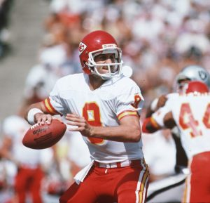 Kansas City Chiefs quarterback Bill Kenney (9) gets ready to throw the ball during a 1985 NFL game against the Los Angeles Raiders.
