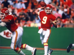 Former Kansas City Chiefs player Bill Kenney (9) drops back for a pass during a game.