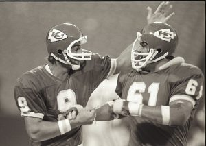 Kansas City Chiefs quarterback Billy Kenney (9) celebrates with his teammate nose tackle Don Parrish (61) during a 1980 NFL game.