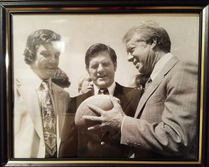 A photo of President Carter accepting a football from Coach Powers.